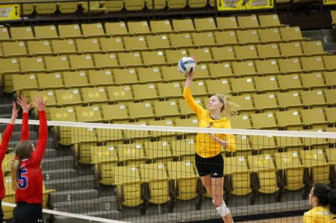 Reagan Karlin spikes the ball over the net to get a kill.
